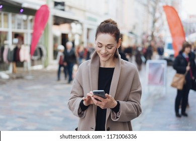 Street portrait of young cheerful woman wearing grey coat using phone