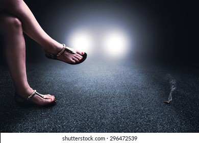 street prostitute crossing legs waiting for client in the night