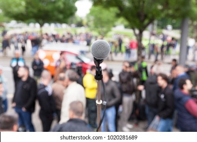 Street protest. Public demonstration. Microphone in focus against blurred people.