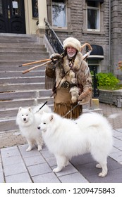 Grande-Allée street, Quebec City, Quebec, Canada, October 21, 2018 - Middle-aged public entertainer dressed in traditional trapper's clothes walking with his two beautiful Samoyed dogs