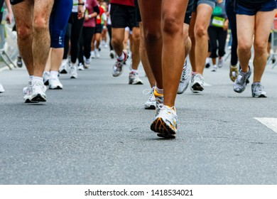 Street racing marathon - legs and tennis running on the asphalt