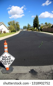 street repair. Fresh slurry or blacktop on surface streets. road work filling pot holes and cracks. fresh oil.
