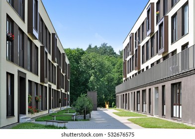 Street of a residential district with modern apartment buildings and trees in perspective.