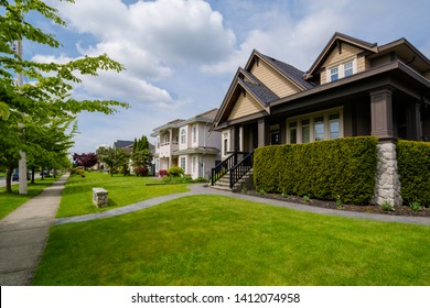 Street of residential houses with concrete pathways and green lawns in front on cloudy day in Vancouver, Canada