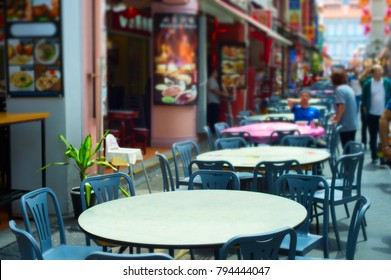 Street restaurant in Chinatown of Singapore. Focus on a table in the foreground