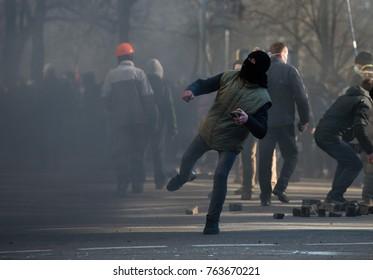 Street riots, a man throws a stone