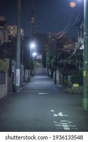 Rue de nuit illuminée par des lampadaires dans un quartier résidentiel de Tokyo.