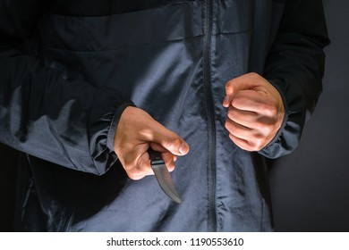 Street robber with a knife - killer person with sharp knife about to commit a homicide, murder scenery