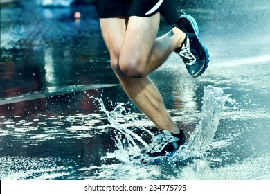 Street runner runs through a puddle