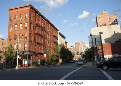 A street runs between mid rise buildings in Manhattan one bright afternoon