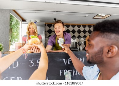 street sale, payment and people concept - happy customers buying burger at food truck