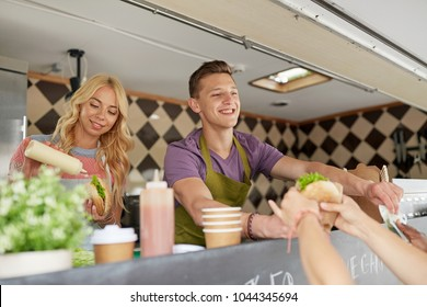 street sale and people concept - happy young sellers serving customers at food truck