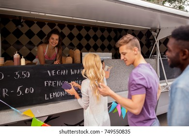 street sale and people concept - happy customers queue at food truck