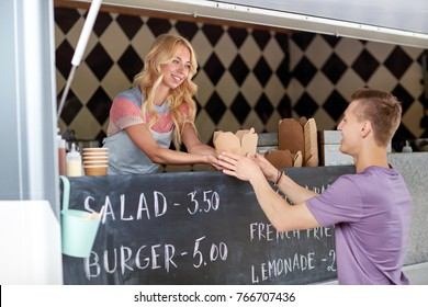 street sale and people concept - happy young saleswoman at food truck serving male customer