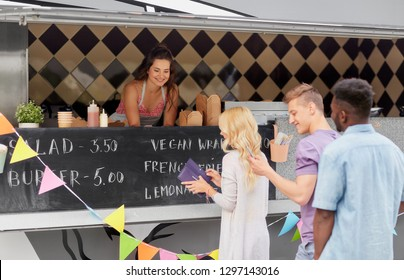 street sale and people concept - queue of customers and happy saleswoman at food truck