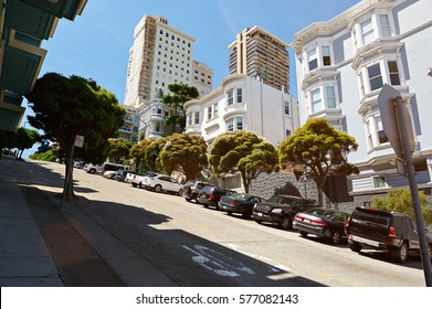 Street in San francisco with road on high hill. Cars parked in modern street