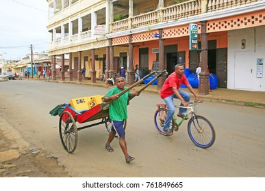 Street scene with a bicycle and a man pulling a rickshaw in Diego Suarez (Antsiranana), Madagascar. Photo taken in Diego Suarez (Antsiranana), Madagascar. March 2013.