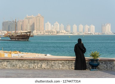 Street scene in Doha, Qatar with lady wearing traditional Qatari black dress and head cover with the Pearl district skyscrapers in the background.