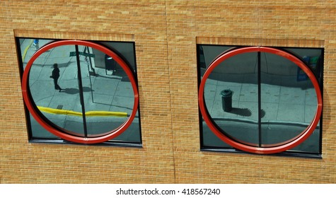 Street scene mirrored in two round windows in a yellow brick wall