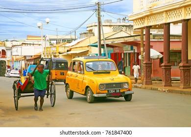 Street scene with an old yellow car and a rickshaw in Diego Suarez (Antsiranana), Madagascar. Photo taken in Diego Suarez, Madagascar in March 2013.