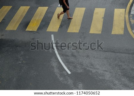 Street scene of pedestrians crossing the road in Kuala Lumpur city center.