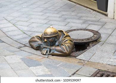 Street sculpture in city Bratislava called Cumil Man at Work.