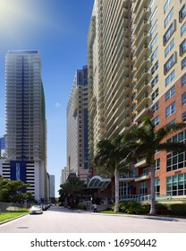 Street in the shore area of downtown Miami on a sunny summer's day. The street shows palm trees, cars, hotels, apartment buildings, some pedestrians, and stores.