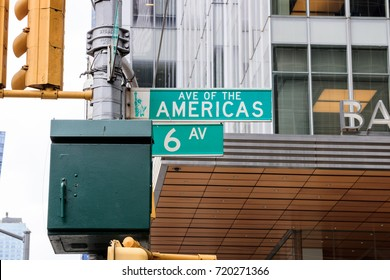 Street sign of 6 Avenue in Manhattan, New York City. Ave of the Americas direction road sign in green color