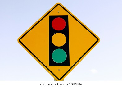 Street sign against a washed out sign indicates a traffic signal ahead.