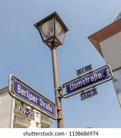 street sign Berliner and Dom Street in Frankfurt under blue sky