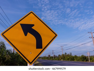 street sign curve and blue sky.