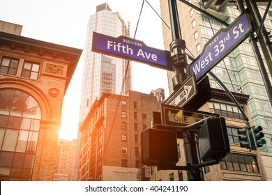 Street sign of Fifth Ave and West 33rd St at sunset in New York City - Urban concept and road direction in Manhattan downtown - American world famous capital destination on warm dramatic filtered look