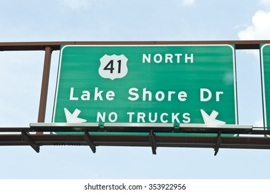 Street sign mentioning Lake Shore Dr, which is a freeway expressway running along the Lake Michigan shoreline in Chicago, Illinois. The signboard mentioned no trucks are allowed.