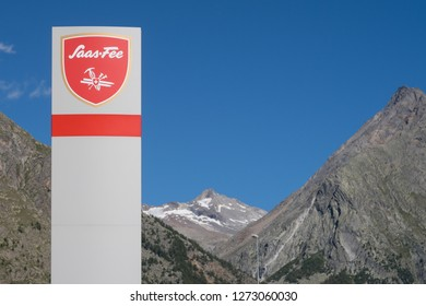 Street sign with the name Saas-Fee on it, a popular wintersports city in Switzerland with mountains and a blue sky on the background