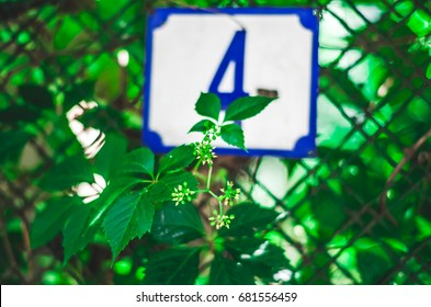 Street sign with number 4 against a wire fence with plants