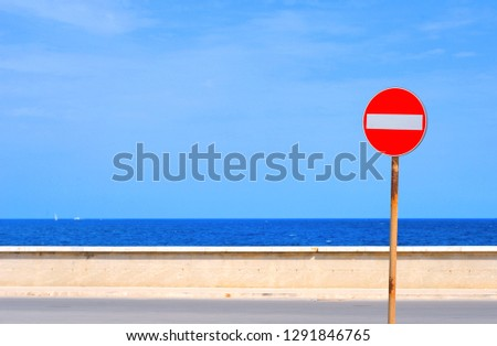Street sign on a empty road with sea and sky in background. no entry. wrong way.