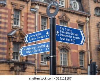 Street sign on Fairfield street indicating City Center, Piccadilly Gardens and Universities Palace Theatre. Typical architecture in the background.