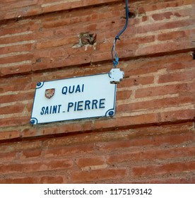 Street Sign on Old European Pinkish, Red Brick Building in Toulouse, France, Street Name Quai Saint Pierre.