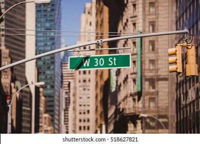 Street sign on W 30 St in New York City - Urban concept in Midtown Manhattan.
