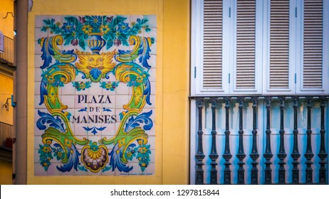 The street sign of Plaza De Manises. The photo shows a place on the facade of the governmental building of the Palau De La Batlia. The photo was taken in the evening in the popular Manises square.