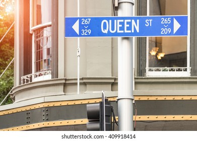 Street sign of Queen Street in Auckland - Urban concept and road direction in the biggest city of New Zealand - Australasian world famous destination with warm filter and enhanced sunshine halo