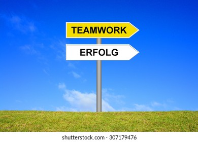 Street Sign showing teamwork and success in german language in front of blue sky on green grass