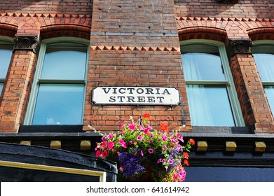 """Street sign """"Victoria Street"""" on the brick building  with beautiful flower below in Liverpool city, England"""