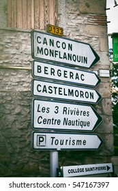 Street signs against stone brick wall in Casseneuill, France, Aquitaine region