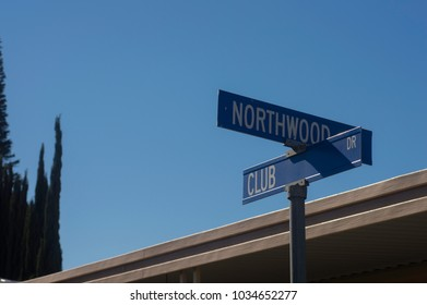 Street signs in Fullerton, CA against a blue sky.