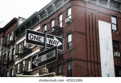 Street signs that show one way in front of brick building.