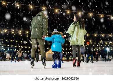 Street skating rink. Family at the ice rink. It snows.