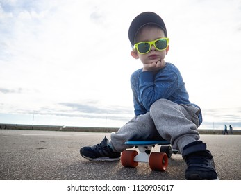 Street sports for children: A small boy in a cap and in sunglasses sat down on a blue penny board to relax.
