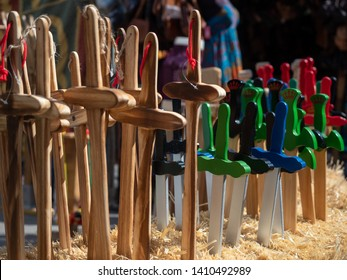 Street stall in a medieval market with wooden swords for children to buy and play.