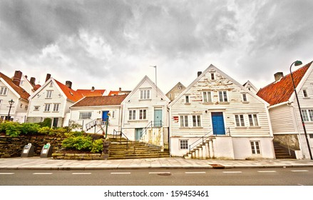 Street in Stavanger, Norway with old, wooden houses in a row and cloudy sky